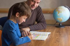 Отец и сын разрешая домашнюю работу математики совместно стоковое изображение rf
