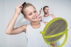 Отец и сын расчесывая волосы стоковое изображение rf