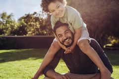 Отец и сын сидя в парке стоковая фотография