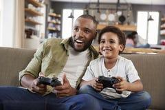 Отец и сын сидя на софе в салоне играя видеоигру стоковая фотография