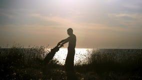 Отец и сын силуэта счастливый играя на пляже на заходе солнца Папа держа его руки ребенка закручивая его вокруг
