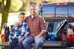 Отец и сын сидя внутри выбирают вверх тележку на располагаясь лагерем празднике Стоковое фото RF