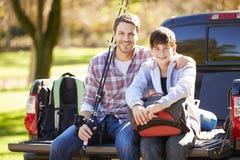 Отец и сын сидя внутри выбирают вверх тележку на располагаясь лагерем празднике Стоковые Изображения RF