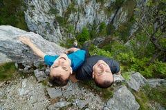 Отец и сын сидя на краю скалы Стоковое фото RF