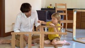Отец и сын собирают деревянную мебель от небольших частей Мальчик помогает его отцу собрать стул видеоматериал