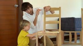Отец и сын собирают деревянную мебель от небольших частей Мальчик помогает его отцу собрать стул акции видеоматериалы