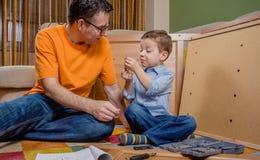 Отец и сын собирая новую мебель для дома Стоковая Фотография RF