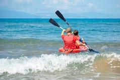 Отец и сын сплавляясь на каяке в океане Активные каникулы с молодым парнем Деятельность при праздника с ребенком школьника стоковое фото rf