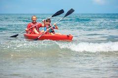 Отец и сын сплавляясь на каяке в океане Активные каникулы с молодым парнем Деятельность при праздника с ребенком школьника стоковая фотография