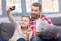 Отец и сын с газетой и smartphone стоковое фото rf
