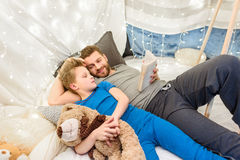 Отец и сын с книгой чтения плюшевого медвежонка в форте одеяла стоковое фото
