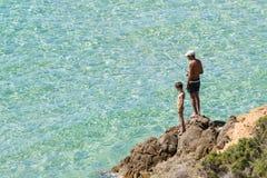 Отец и сын удят от утесов в прозрачном море Сардинии Стоковое фото RF