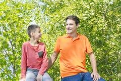Отец и сын усмехаются в парке лета Стоковое Изображение