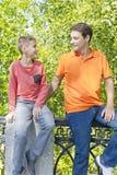 Отец и сын усмехаются в парке лета Стоковые Фотографии RF