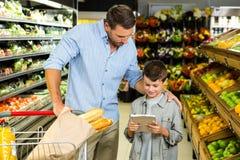 Отец и сын читая список бакалеи Стоковые Фотографии RF