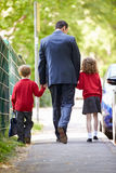 Отец идя к школе с детьми на пути работать стоковые изображения