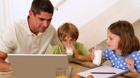 Отец и дети используя компьтер-книжку совместно на таблице завтрака Стоковая Фотография
