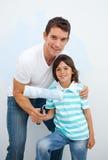 отец мальчика его paiting усмехаться комнаты Стоковое Изображение