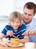 отец мальчика жадный его мед кладя waffles Стоковая Фотография RF