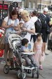 Отец, мать и 3 дет смотря в трассе телефона вокруг цирка Piccadilly Стоковое Изображение RF