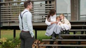 Отец наблюдает как жена и дочери сидят на шагах сток-видео