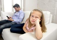 Отец наркомана интернета используя мобильный телефон игнорируя маленькую унылую дочь пробурил сиротливое и подавленное Стоковые Изображения
