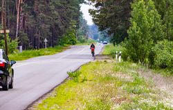 Отец носит дочь на велосипеде на шоссе стоковые фотографии rf