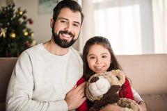 отец обнимая дочь с плюшевым медвежонком и смотреть стоковое изображение rf