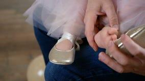 Отец помогает положить дальше ботинки его дочь, она сидя на его коленях сток-видео