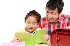 Отец помогая его daugther делая домашнюю работу Стоковое Изображение