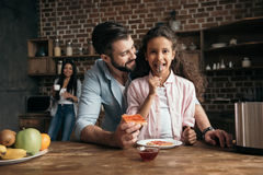 Отец помогая маленькой дочери подготавливая здравицы с вареньем Стоковые Изображения