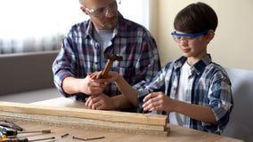 Отец помогая меньшему милому сыну на мастерской, умном ребенке бить молотком ноготь молотком в древесине стоковое изображение rf