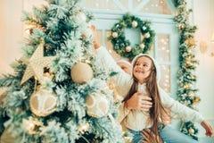 Отец порции девушки украшая рождественскую елку, держа некоторые безделушки рождества Стоковая Фотография RF