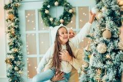 Отец порции девушки украшая рождественскую елку, держа некоторые безделушки рождества Стоковая Фотография