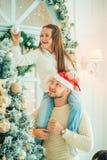 Отец порции девушки украшая рождественскую елку, держа некоторые безделушки рождества Стоковые Изображения