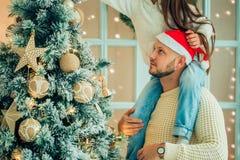 Отец порции девушки украшая рождественскую елку, держа некоторые безделушки рождества Стоковые Фотографии RF