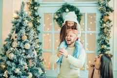 Отец порции девушки украшая рождественскую елку, держа некоторые безделушки рождества Стоковые Фото