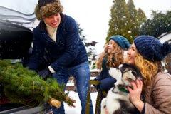 Отец принес рождественскую елку в хоботе автомобиля SUV к дочери, матери и собаке для того чтобы украсить домой Семья подготавлив стоковое фото rf