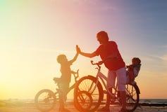 Отец при дети велосипед на заходе солнца Стоковые Фото