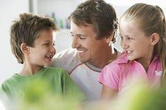 Отец при дети усмехаясь дома стоковое изображение