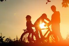 Отец при 2 дет ехать велосипед на заходе солнца Стоковые Фото