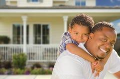 Отец смешанной гонки и сын перед домом стоковое изображение rf
