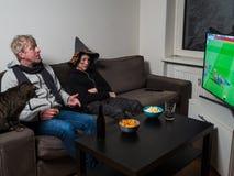 Отец, сын и кот смотря футбол кубка мира футбола на ТВ стоковые фотографии rf