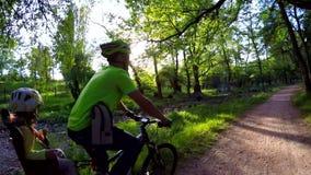 Отец с малым велосипедом катания ребенка в зеленом парке акции видеоматериалы