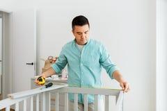 Отец с ПК планшета и кроватью младенца правителя измеряя стоковое фото