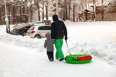 Отец с ребенком в костюмах зимы идет вниз с холма с плюшкой для ехать в снеге в руках к парковке к его автомобилю стоковая фотография rf