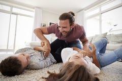 Отец щекоча детей по мере того как они играют игру в салоне совместно стоковое изображение rf