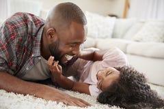 Отец щекоча дочь по мере того как они играют игру в салоне совместно стоковая фотография rf