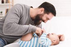 Отец щекоча и snuggling его сына младенца стоковая фотография