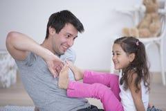 Отец щекоча ногу дочери дома Стоковые Фотографии RF